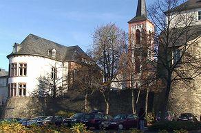 Bitburg – Teile der alten Römermauer mit der Kirche im Hintergrund