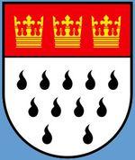 Kölner Stadtwappen – Im Zuge der Gegenreformation wurde der Kult der Hl. Ursula durch die Jesuiten wiederbelebt und das bis dato blanke silberne Feld um die 11 Hermelinschwänze erweitert.