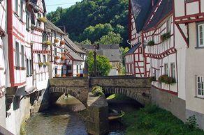 Monreal – Fachwerkhäuser an der Elz, im Hintergrund die Steinbrücke mit dem Löwendenkmal